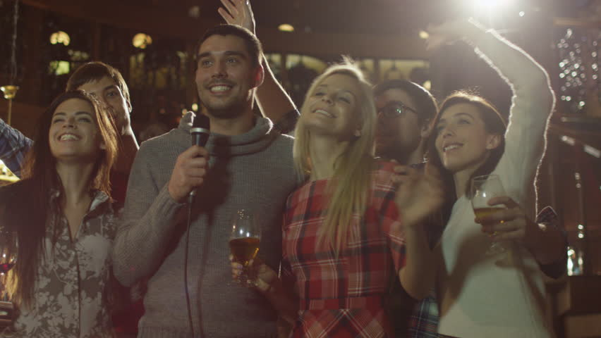 Friends are singing karaoke songs while having a good time together at a bar. Shot on RED Cinema Camera in 4K (UHD).