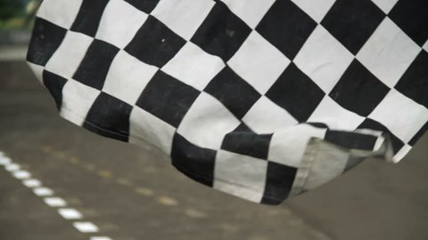 Waving race checkered flag in race track