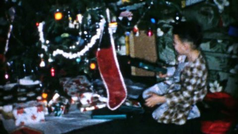 AKRON, OHIO, DECEMBER 25, 1956: A little boy opens presents on Christmas morning in 1956.