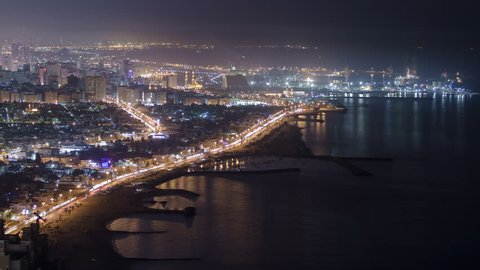 Panoramic view of Sharjah coastline at night from Ajman rooftop timelapse - third largest and most populous city in United Arab Emirates. Sharjah is located along northern coast of Persian Gulf on