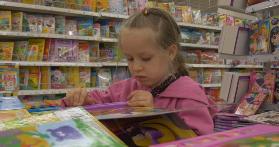OPOLE/POLAND - MAY 08 2015: Baby Girl In A Supermarket Choose Book ...