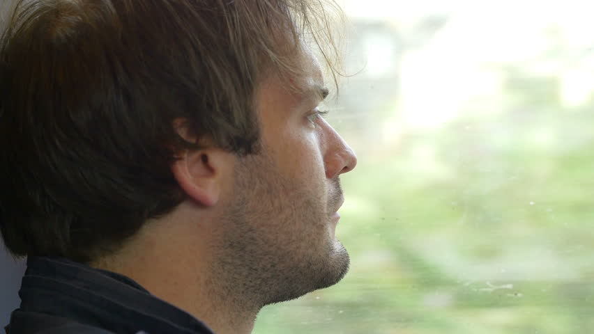 Sitting on the train and travelling: young pensive man looking out the window | Shutterstock HD Video #13444613