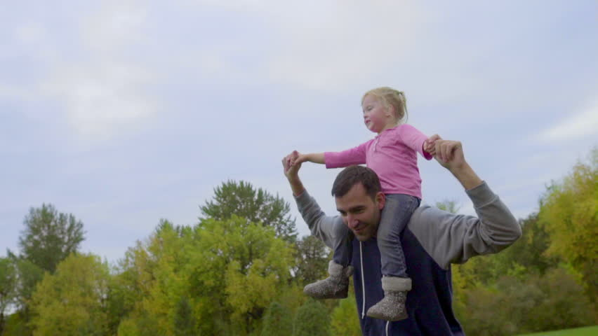 Dad jogs a little with his little girl on his shoulders