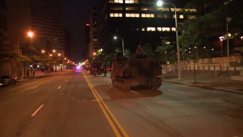 CIRCA 2010s - Police and Marines roll out tanks and armored vehicles through an American city during times of public unrest and rioting.