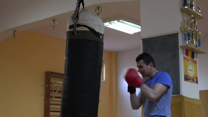 Teen Adult Having Fun Hitting Punching Bag With Fists Using Boxing Mittens  4K   4K Stock