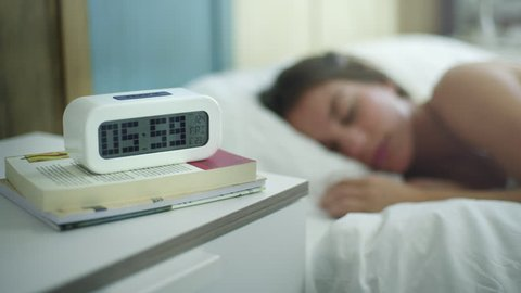 Young woman is sleeping in the morning when ring the alarm. She switch off it and continue sleeping.