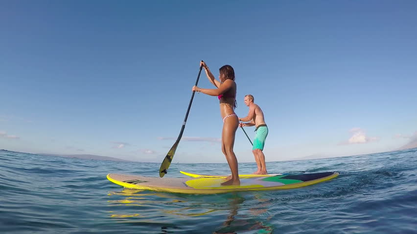 Couple Stand Up Paddling In Ocean on Summer Day