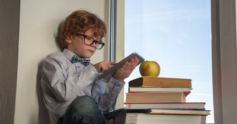 Little Genius Comprehend Science. Auburn curly boy with glasses sitting on a windowsill with a tablet and books. In the pile of books lies the big apple. Boy thoughtfully takes it in his hands