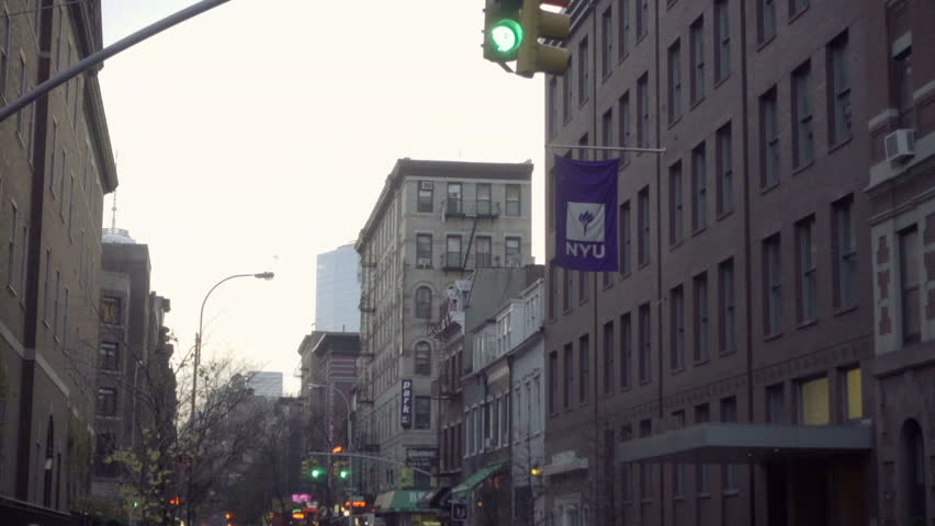 NEW YORK - DEC 6, 2015: NYU flag in West Village, people on street, students, kids and couple, stroller in afternoon on cold day, NYC. Washington Square serves as the university's main campus.