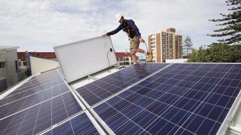 Solar technician installing solar panels on roof.