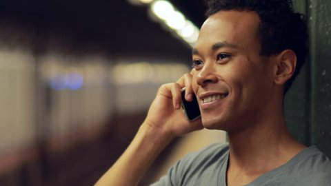 Young man in New York City in subway station platform talking on cell phone