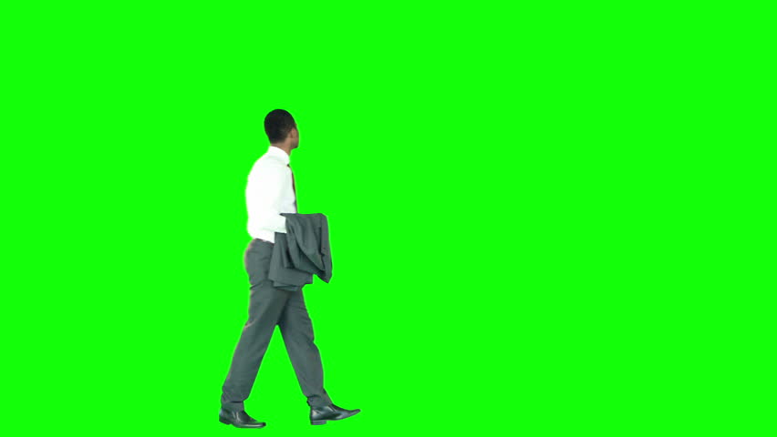 Businessman with jacket in hand walking against green background | Shutterstock HD Video #13709504