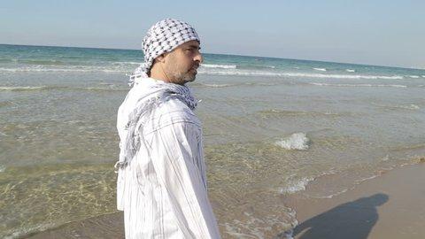 Shot of Arab in jalabiya walks along the sea shore