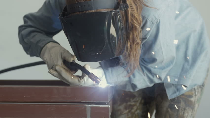 Woman welder welding metal framework.  | Shutterstock HD Video #13715735