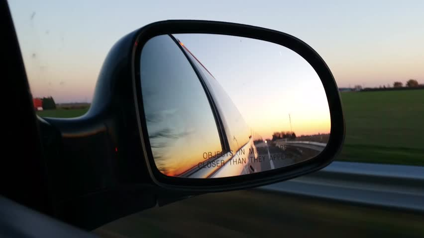 Side View Mirror looking backwards driving on highway in vehicle