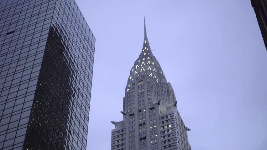 NEW YORK - DEC 15, 2015: Chrysler Building at night skyscraper lights tilting down to American flag on office buildings, East 42nd st in 1080 HD NY. Art Deco architecture is used in Midtown Manhattan.
