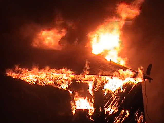 Flames engulfing a house at night