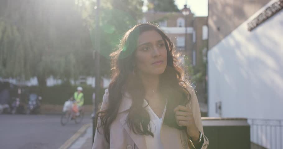 Beautiful Indian woman walking through city living happy lifestyle using smart phone reading social media | Shutterstock HD Video #13831955