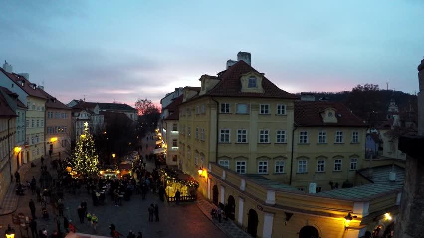 Prague Christmas market camera pan upstairs from Charles Bridge early evening sun down and a lot of people visiting small market also showing the warm yellow light of lantarns and people browsing 4k