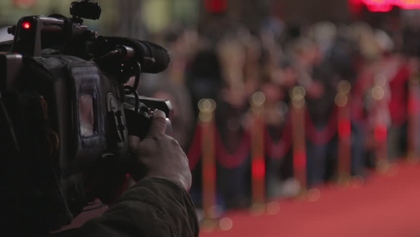 Videographer shoots festive event. A professional cameraman shoots video while passing celebrities on the red carpet