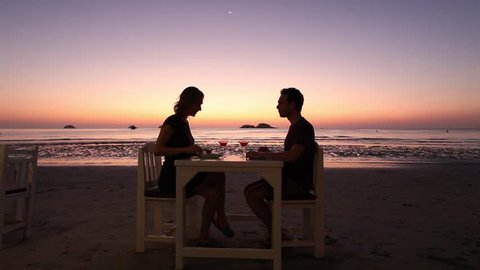 beautiful romantic dinner on the beach in luxury restaurant, couple on honeymoon drinking fruit cocktails near the sea