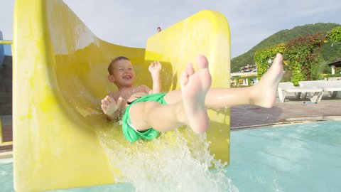 SLOW MOTION: Happy kid smiling sliding down the toboggan with hands raised in aquapark on a beautiful sunny day in summer