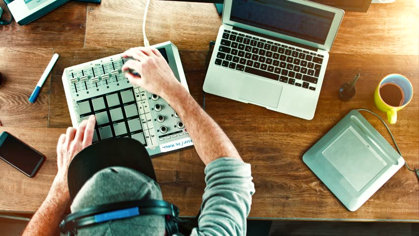 Cinemagram / Cinemagraph: Music Producer / DJ working with his Drum Machine / mixer on old wood table, desktop - overhead top shot