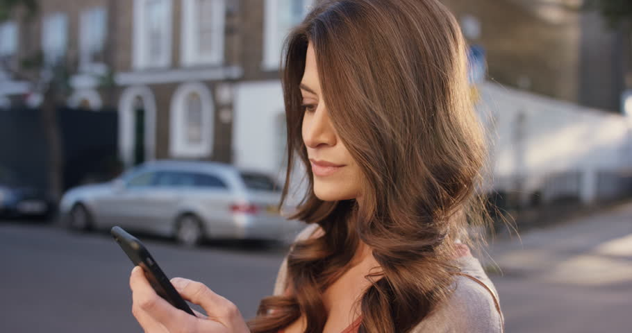 Beautiful woman using smart phone technology app in city streets living urban happy lifestyle | Shutterstock HD Video #13909415