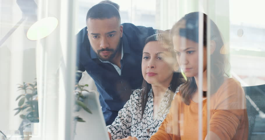 Creative business team meeting in modern start up office female team leader pointing at screen slow motion dolly camera movement around reflective open plan glass office | Shutterstock HD Video #13966055