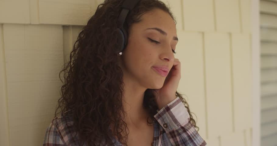 A beautiful young hispanic woman wearing headphones #13973435