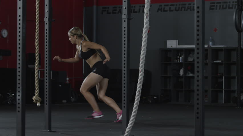 A woman doing sprints inside of a gym with workout equipment in the foreground - fitness / crossfit / exercise / workout