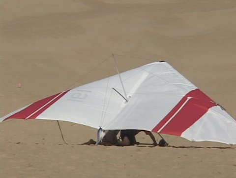 A hang-glider falls into the sand after an unsuccessful trial run.