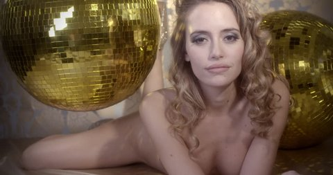 stunning sexy disco woman poses naked, surrounded by gold disco balls