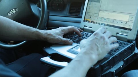 Anaheim, CA., January 2016: Police man typing on his laptop inside his patrol car
