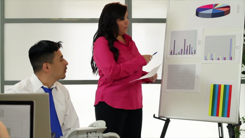 A pretty Hispanic woman giving a presentation to her team members or marketing something to potential clients.