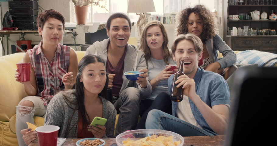 Happy diverse group of student sports fans throwing arms up in excitement celebrating goal watching sports event on TV together bonding as friends eating snacks drinking beer | Shutterstock HD Video #14075177
