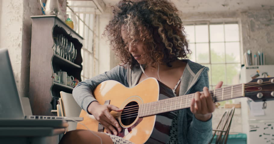 Attractive curly haired mixed race young girl sitting on wooden chair at a window wearing a grey hoodie concentrating focused learning to play guitar using laptop computer at home | Shutterstock HD Video #14075474
