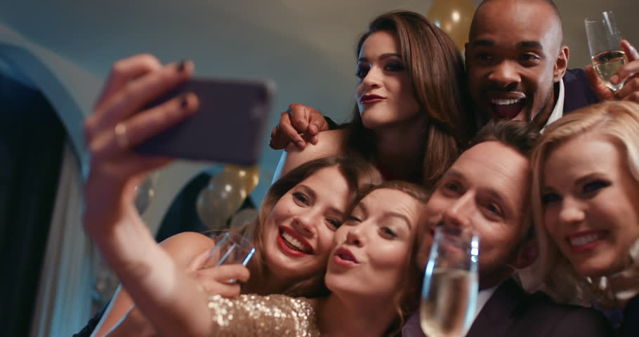 smiling group of friends celebrating evening event taking selfie at glamorous fashion party drinking champagne