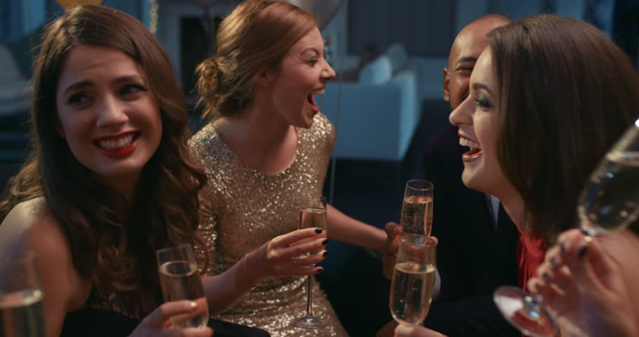 Friends holding up champagne flutes together in a toast at sexy glamorous party celebration cheers   Shutterstock HD Video #14076065
