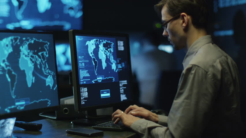 IT professional programmer in glasses is working on computer in cyber security center filled with display screens. Shot on RED Cinema Camera in 4K (UHD).