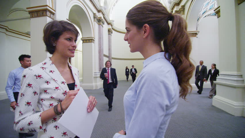 Diverse group of business or political delegates meeting in an elegant, classically designed building. Two attractive young businesswomen stand and chat with others walking past them. In slow motion.   Shutterstock HD Video #14100995