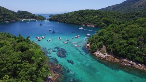 Famous blue lake (lagoa azul) dive area, with a transparent water and touristic boats discovering the archipelago. Aerial drone view, Ilha Grande (Big Island), Angra dos Reis - Rio de Janeiro - Brazil