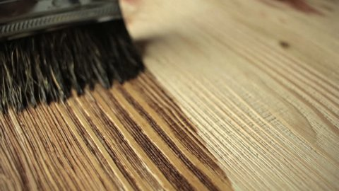 Close-up Wood painting with a brush with the brown color