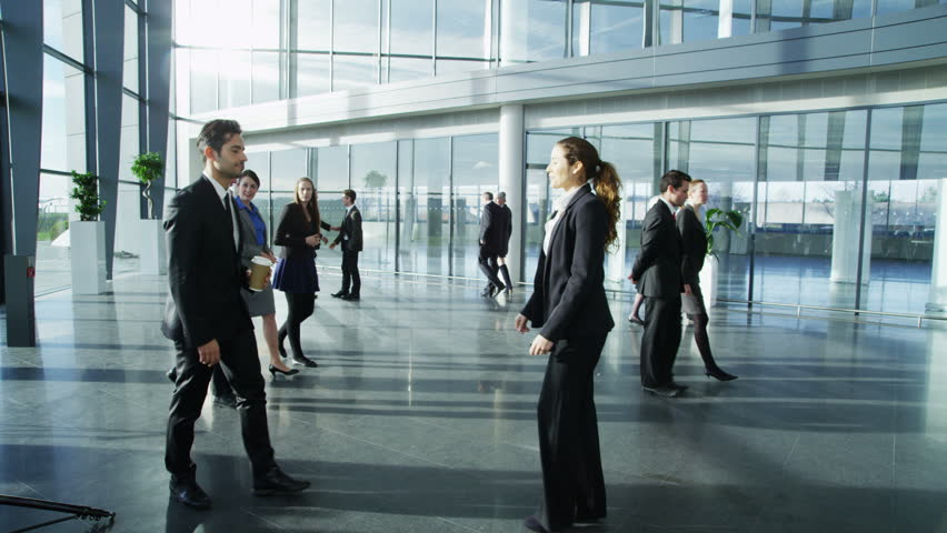 4k / Ultra HD version Attractive young businessman and businesswoman meet and shake hands in a busy modern office building. Other workers can be seen walking around the building . Shot on RED Epic | Shutterstock HD Video #14128085