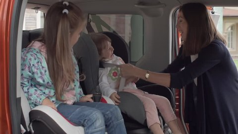 Young mother putting her little daughter in the baby car seat and fasten seat belts
