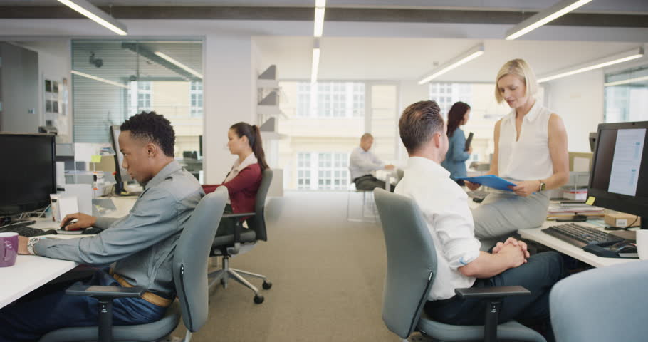 Busy activity in diverse business office with business people working multi tasking in workplace discussing growth ideas and networking with technology | Shutterstock HD Video #14142935