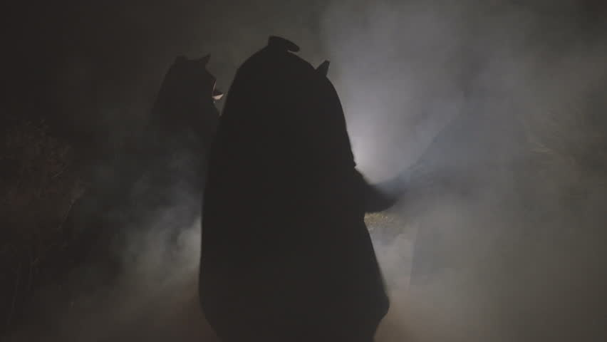 Witch silhouette hexing in dark smoke