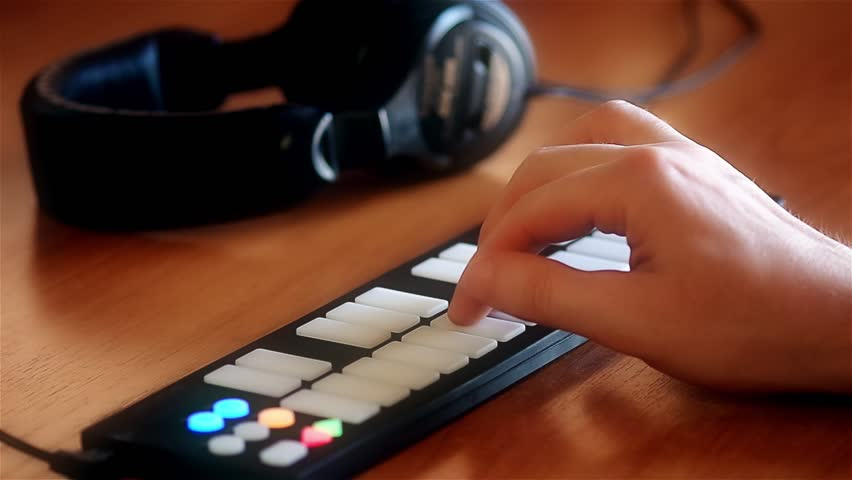 Playing on a MIDI keyboard with light up buttons and headphones laying aside defocused | Shutterstock HD Video #14149235