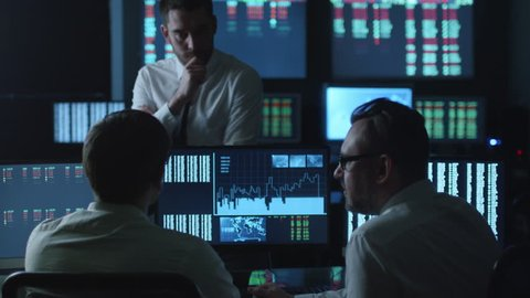 Team of stockbrokers are having a conversation in a dark office with display screens. Shot on RED Cinema Camera in 4K (UHD).
