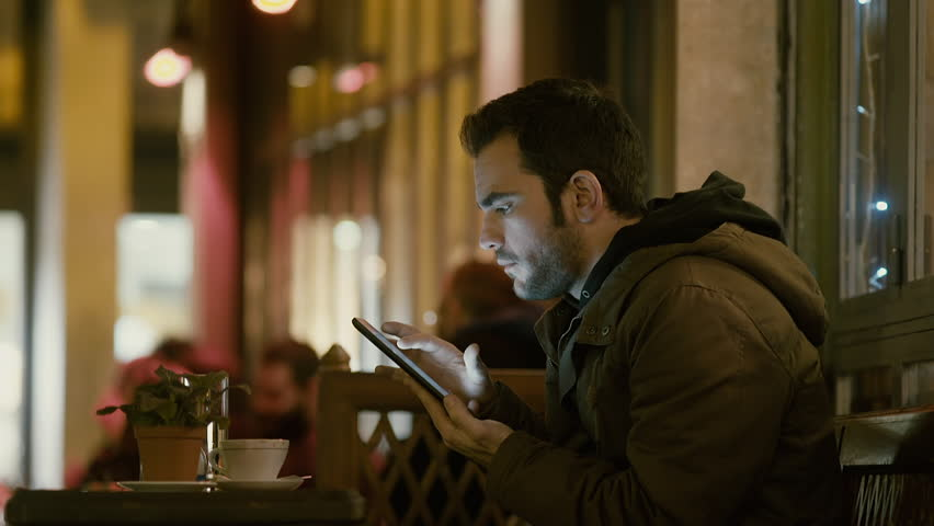 Young man sitting in night cafe/bistro browsing with tablet with a serious face, outside at winter at night after work drinking coffee and browsing his sites and social media on his tablet. | Shutterstock HD Video #14190695
